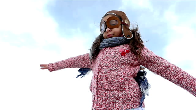 Little girl with pilot hat playing spreading arms like an airplane against blue sky, slow motion video