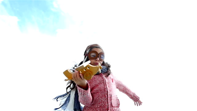 Little girl with pilot hat playing with wooden airplane against blue sky, slow motion video
