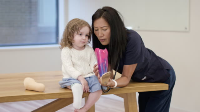 Little girl with prosthetic leg at medical appointment A happy preschool age girl is at a medical appointment. She is sitting on an examination table. The child has a prosthetic leg. Her Asian physical therapist is speaking to the child and examining the leg. The child is smiling and happily interacting with her medical provider. orthopedic equipment stock videos & royalty-free footage