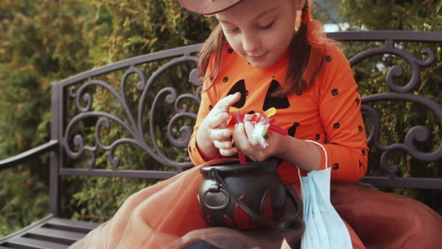 Little girl with protective face mask looking into her basket with candies and sweets on Halloween Little girl on Halloween during COVID-19 pandemic. BMPCC 4k video. halloween covid stock videos & royalty-free footage