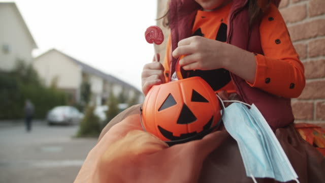 Little girl with protective face mask looking into her basket with candies and sweets on Halloween Little girl on Halloween during COVID-19 pandemic. BMPCC 4k video. candy stock videos & royalty-free footage