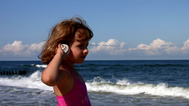 Little girl with shell at the beach Little girl with shell at the beach animal shell stock videos & royalty-free footage