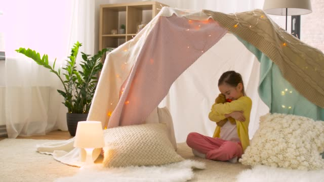 vídeos de stock e filmes b-roll de little girl with teddy bear in kids tent at home - hygge