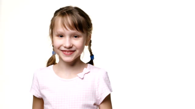 little girl with two braids looking at camera smiling - solo una bambina femmina video stock e b–roll