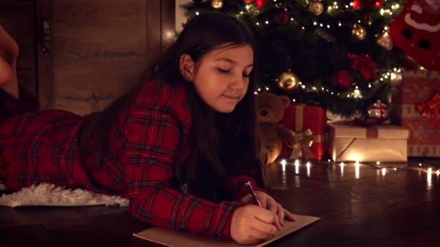 vídeos y material grabado en eventos de stock de niña escribiendo una carta a santa claus - deseo