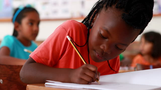 Little girl writing and smiling at camera during class