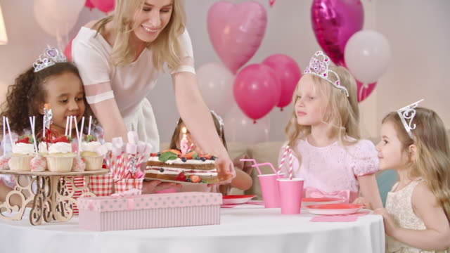 Little Girls Blowing Out Candle on Birthday Cake Mother putting birthday cake on table and little girls dressed like princesses blowing out candle on it princess stock videos & royalty-free footage