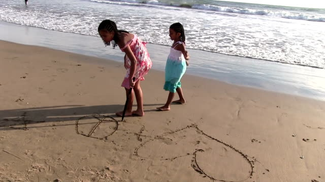 Little girls drawing in sand on beach video