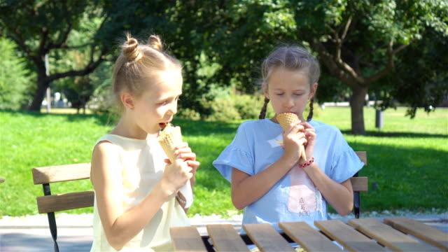 vídeos de stock, filmes e b-roll de meninas, comer gelado ao ar livre no verão no café ao ar livre - gelato