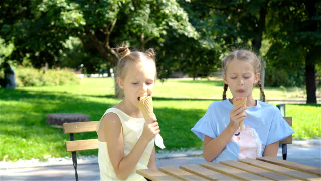 vídeos de stock, filmes e b-roll de meninas que comem o gelado ao ar livre no verão no café ao ar livre - gelato