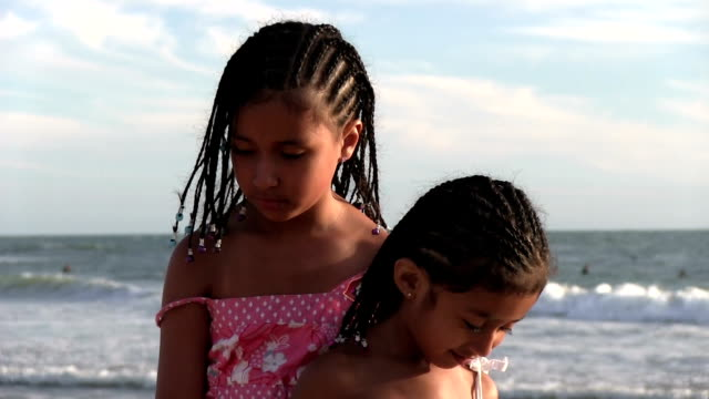Little girls making sad and happy faces on beach video