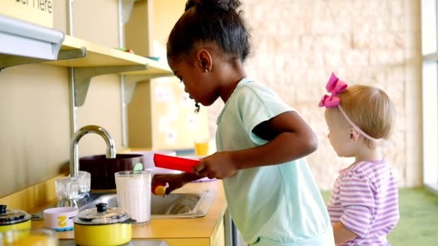 little girls participate in creative play in a toy kitchen - giocattolo video stock e b–roll