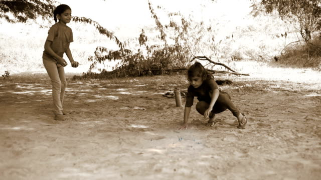 Little girls playing Marbles HD1080p : Two little girls of Indian ethnicity sitting on ground & playing marbles. sepia toned stock videos & royalty-free footage