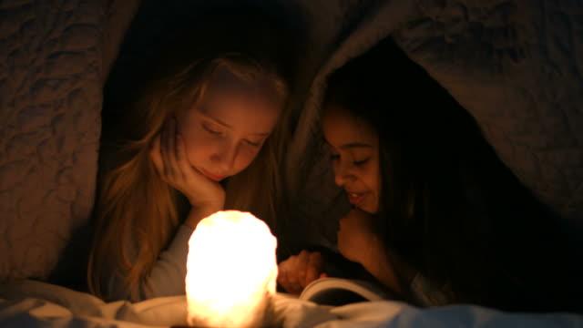 little girls reading book under blanket at night - personaggio fantastico video stock e b–roll