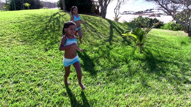 Little girls running on grass near beach video