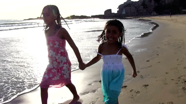 Little girls skipping holding hands at bruja beach during sunset video