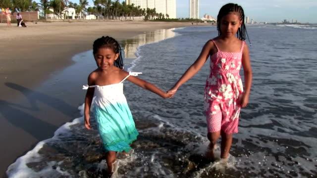 Little girls walking holding hands at bruja beach during sunset video