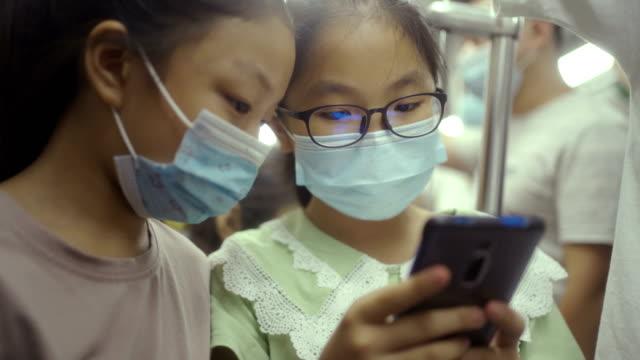 vídeos de stock e filmes b-roll de little girls with mash in metro - extremo oriente