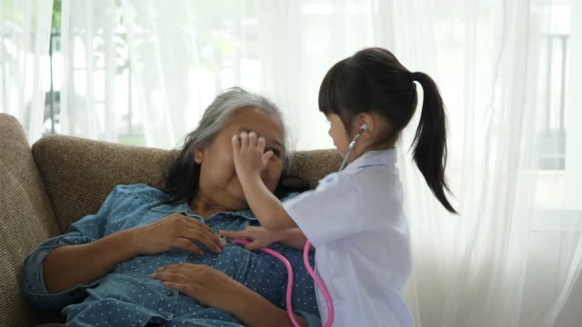 Little granddaughter dressed in medical uniform playing as a doctor with grandmother at home video