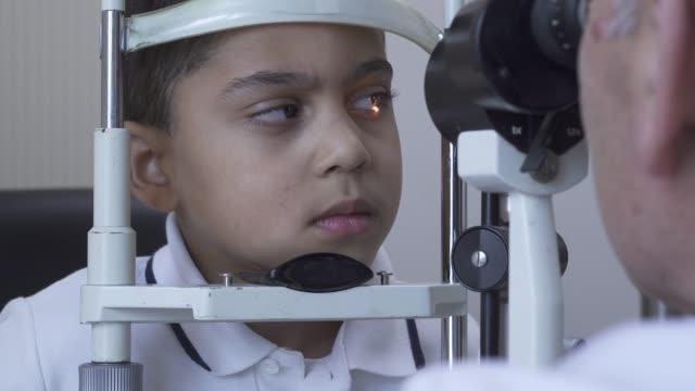 vidéos et rushes de petit beau garçon de biche de test d'oeil à la clinique s'asseyant devant le docteur - réfracteur