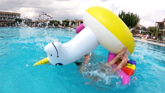 vídeos de stock, filmes e b-roll de menina feliz e a mãe dela flutuando sobre um unicórnio inflável na piscina - inflável