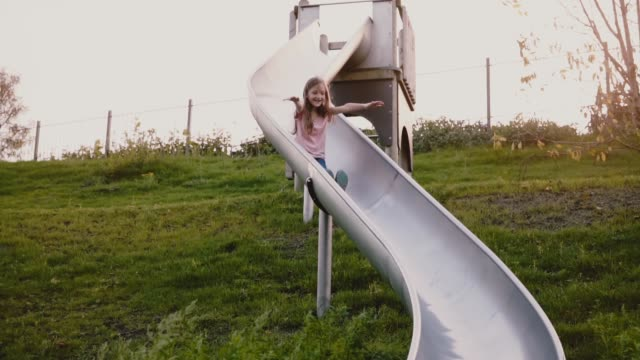 little happy girl goes down a sliding board. slow motion. cute female child with long hair on summer green playground - slitta video stock e b–roll
