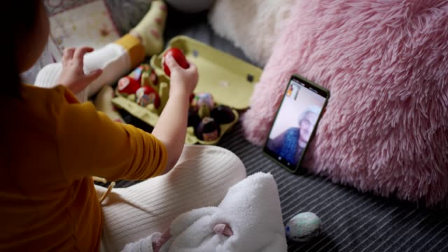 Little joyful girl enjoying Easter with her grandmother over a video call