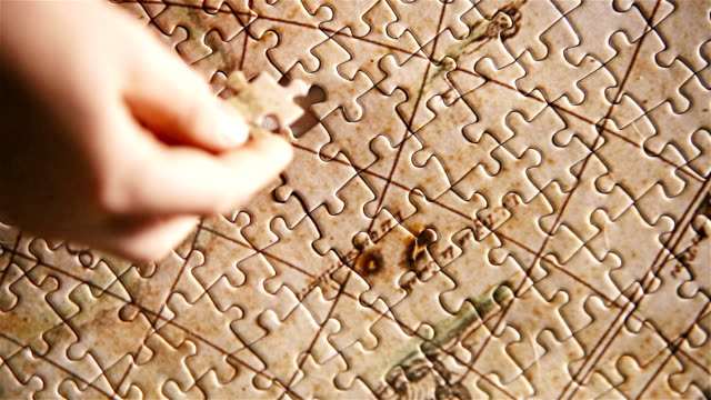 little kid completed the puzzle world map. last piece inserting moment. - puzzle video stock e b–roll