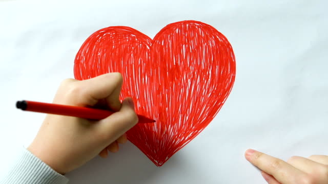 Little kid drawing big red heart and making word love of cubes, kindness, peace