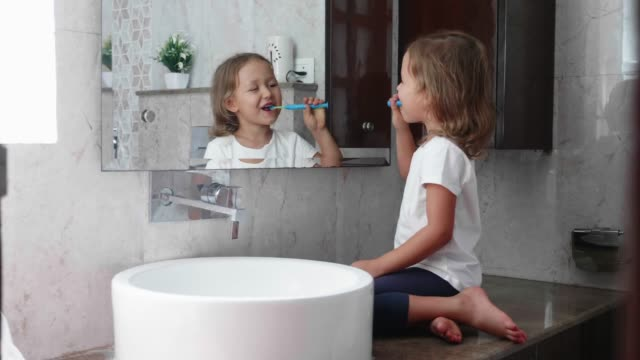 vídeos de stock e filmes b-roll de little kid girl is brushing her teeth with toothbrush in front of the mirror. - escovar