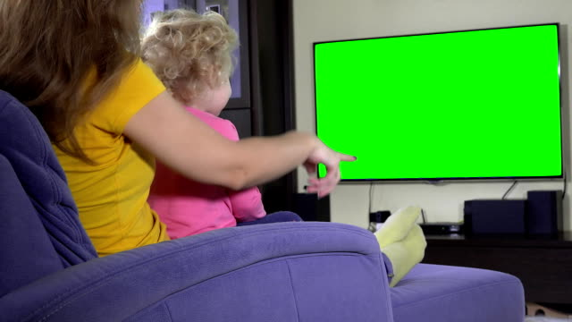 little kid watching TV program with mom. Green chroma key screen little kid watching TV program with mom. Green chroma key screen. Static shot. FullHD FHD shirt stock videos & royalty-free footage