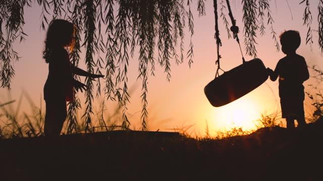 lilla barn, pojke och flicka som leker med swing nära sjön under vackra solnedgången - flod vatten brygga bildbanksvideor och videomaterial från bakom kulisserna