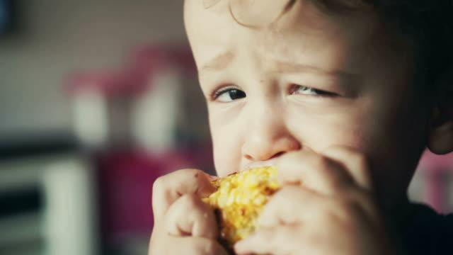 小さなお子様を食べ軸付きとうもろこし - 野菜点の映像素材/bロール
