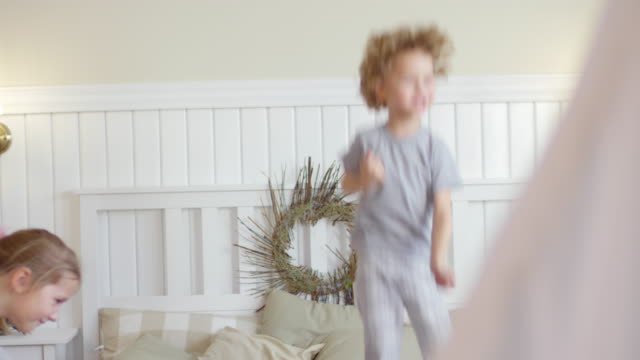Bидео Little Kids Jumping on Bed in Cozy Kids Room with Christmas Decorations