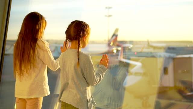 Poco los niños juntos en el aeropuerto a la espera de embarque junto a la ventana grande - vídeo