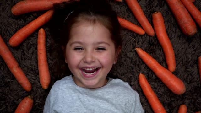 kleines lachendes mädchen entspannt sich, während sie auf ihrem teppich liegt, umgeben von karotten - karotte peace stock-videos und b-roll-filmmaterial