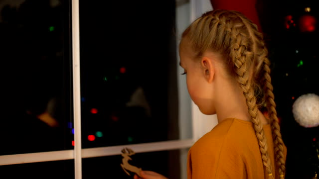 little lonely girl playing with wooden toy near window on orphanage, xmas eve - время дня стоковые видео и кадры b-roll