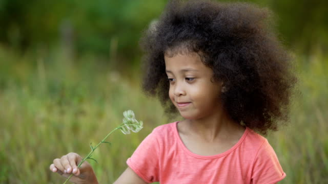 Little lonesome kid standing in garden and playing with small white flower