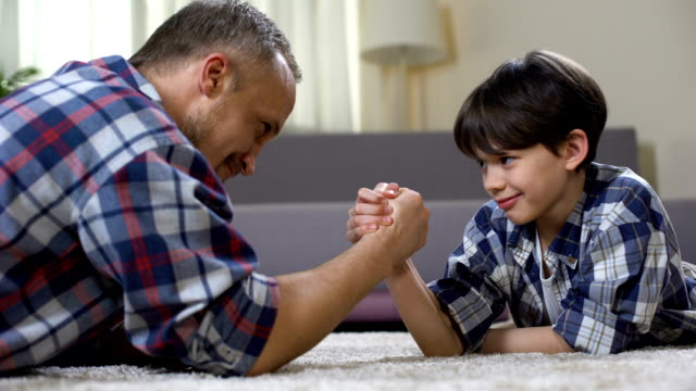 Little male kid challenging his father in arm wrestling, having fun together video