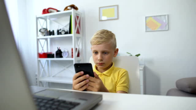 Little male kid sitting in front of laptop and watching video on smartphone, app