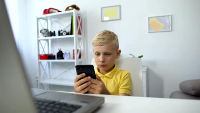 stockvideo's en b-roll-footage met mannetje kid zittend in de voorkant van de laptop en het kijken naar video op smartphone, app - kids online abuse