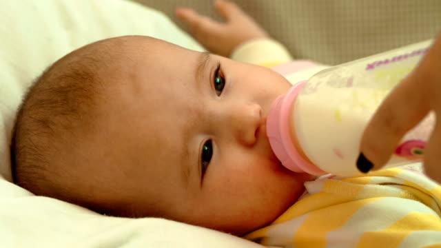 vídeos de stock, filmes e b-roll de pequeno bebê recém-nascido comendo leite da garrafa - bico
