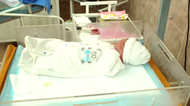 Little newborn baby lying in a cradle in hospital. video
