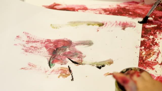 vidéos et rushes de le petit peint un morceau de papier avec le pinceau. - toile à peindre