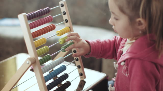 Little preschooler with abacus learning Cute little girl, playing with an abacus at home, sunny living room. stock video...