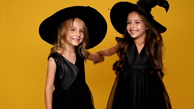 Little pretty friends girl in black witches dresses and decorated hats holding hands each other and smiling over orange background video