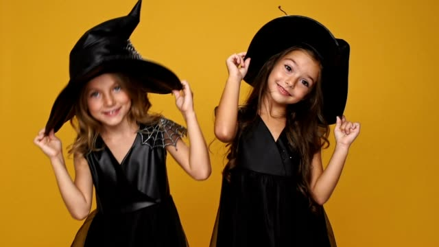 Little pretty girls wearing witch dresses playing with their hats isolated  ovwe orange video f6f33330b22a