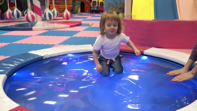 vídeos de stock e filmes b-roll de little pretty toddler girl playing in synthetic pool , jumping, laughing and smiling - brinquedos na piscina