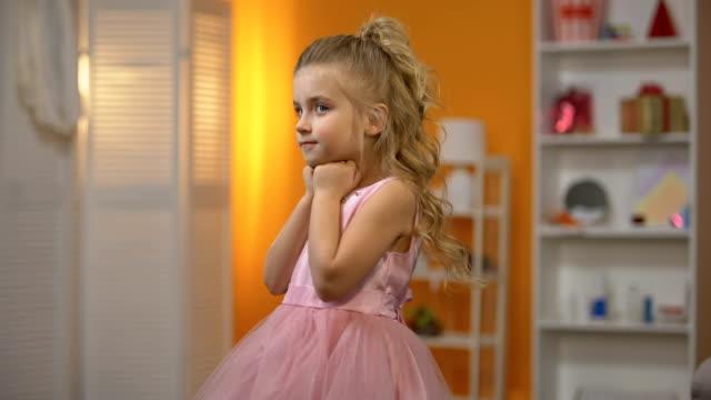 Little princess in adorable pink dress, childhood dream, happy preschool girl