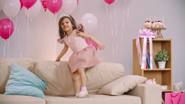 Little Princess Jumping on Sofa Cute little girl jumping on sofa in the living room decorated for birthday party princess stock videos & royalty-free footage